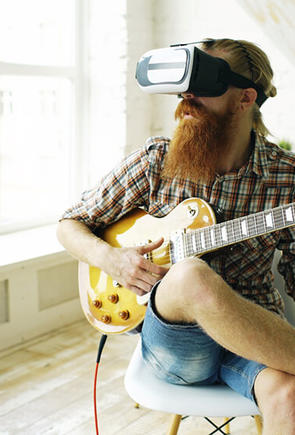 Guy playing guitar wearing VR glasses